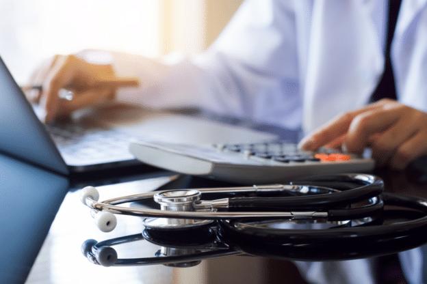 Doctor calculating physician revenue metrics